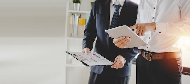 職業訓練。新しいマネージャー上司に立って若いインターン見習い学習統計グラフ、オフィスで働いている若いタブレットにモバイルタブレットでオンライン作業を教える Premium写真