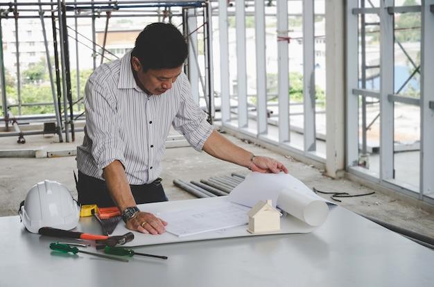 プロの建築家、エンジニアまたはインテリア図面の青写真と建設現場のオフィスセンターの会議テーブルのツール、 Premium写真