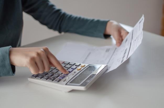 若い女性の分析のための計算機を使用して、ホームオフィスの机の上の家族の予算の費用手形レポートを計算します。 Premium写真