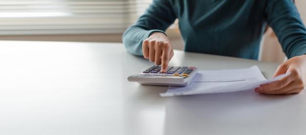Панорамный баннер. рука молодой женщины с помощью калькулятора для расчета стоимости бюджета семейного бюджета на столе в домашнем офисе Premium Фотографии