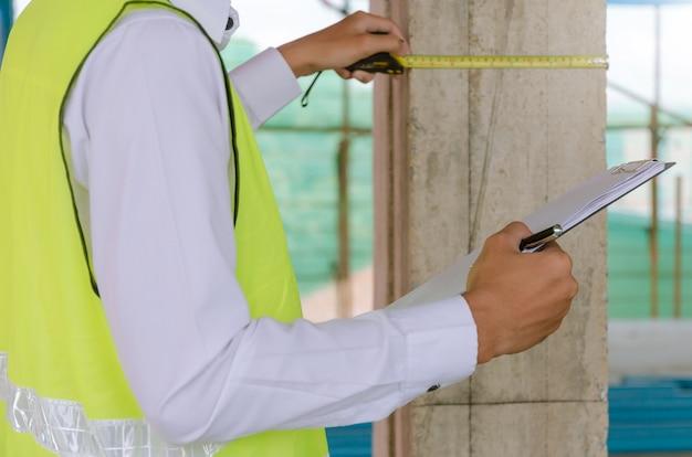 若い職長ビルダーエンジニアまたは検査官チェックとクリップボードで検査し、建設現場の建物で測定テープ Premium写真