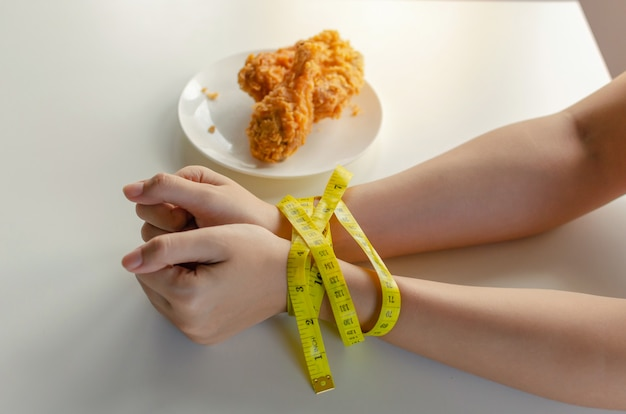 Диета. молодая женщина стройное тело руки связаны желтой рулеткой и вкусной хрустящей жареной курицей в блюдо на столе в кухне дома Premium Фотографии