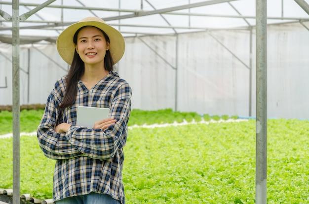 笑みを浮かべて、水耕栽培の新鮮な緑の野菜とモバイルスマートタブレットを保持しているアジアの若いフレンドリーな女性農民が温室の庭の保育園で生産します。 Premium写真