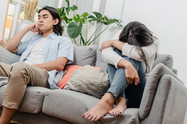 けんかをして、戦いの後ソファーに座っていた悲しみ若いアジアの妻 Premium写真