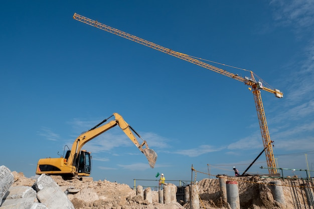 建設現場での掘削機とタワークレーン Premium写真
