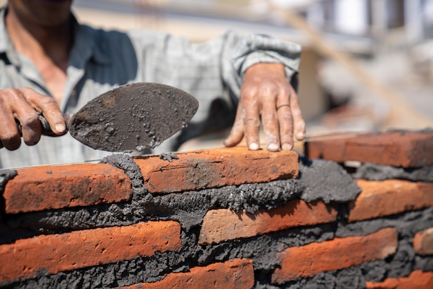 Каменщик промышленный рабочий, установка кирпичной кладки шпателем шпателем на строительной площадке Premium Фотографии