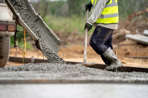 Строительный рабочий заливает мокрый бетон на дорожно-строительной площадке Premium Фотографии