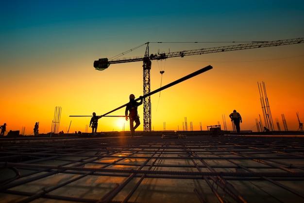 建設現場で鋼鉄製の補強バーを作るシルエット建設労働者 Premium写真