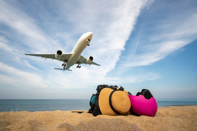 Дорожная сумка на пляже и посадка самолета Premium Фотографии