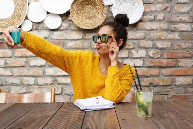 スタイリッシュなアフリカの女性は、カフェでセルフを取って Premium写真