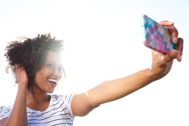 明るい日光に照らして屋外のスマートフォンでセルフを撮っている若い女性に笑顔 Premium写真