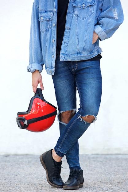 ヘルメットを保持してリッピングジーンズとオートバイの肖像 Premium写真
