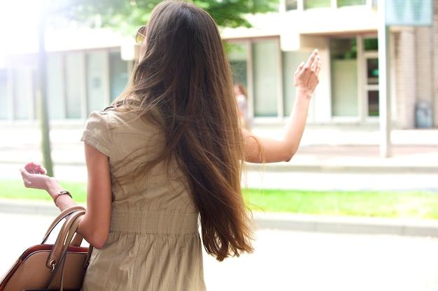 Стильная молодая женщина машет такси Premium Фотографии