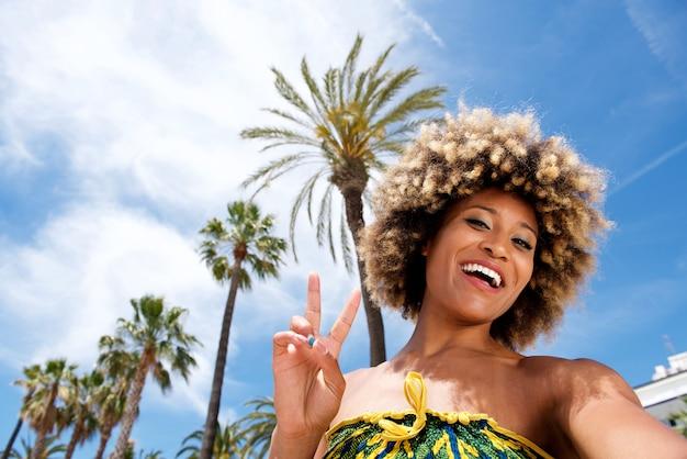 ビーチで休暇をしてセルフジェイとジェスチャーピースサインを撮る美しい若い女性 Premium写真