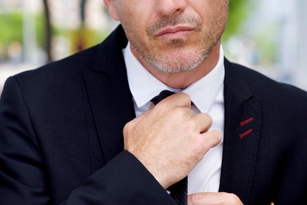 Закройте серьезный бизнесмен корректирующий узел на галстуке Premium Фотографии