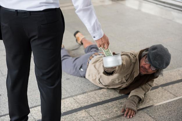 ビジネスマンは、障害のあるホームレスの男性にお金を与える Premium写真