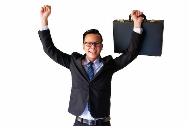 Азиатский бизнесмен держит чемодан и поднимает руки с улыбающимся лицом Premium Фотографии