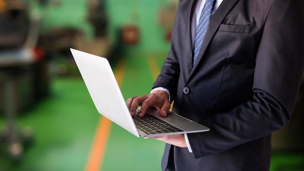 ビジネスマンは工場でラップトップ上で動作します Premium写真
