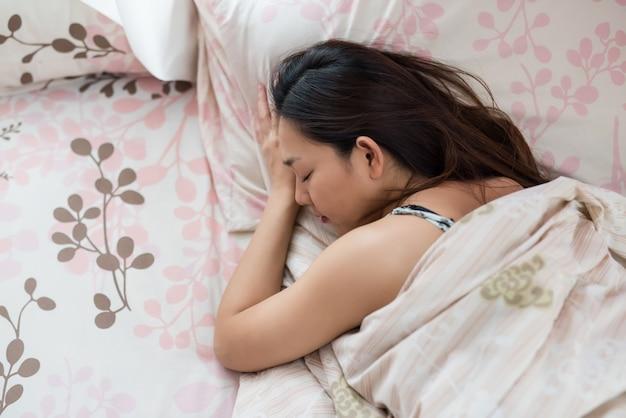 アジアの女性がベッドで寝る Premium写真