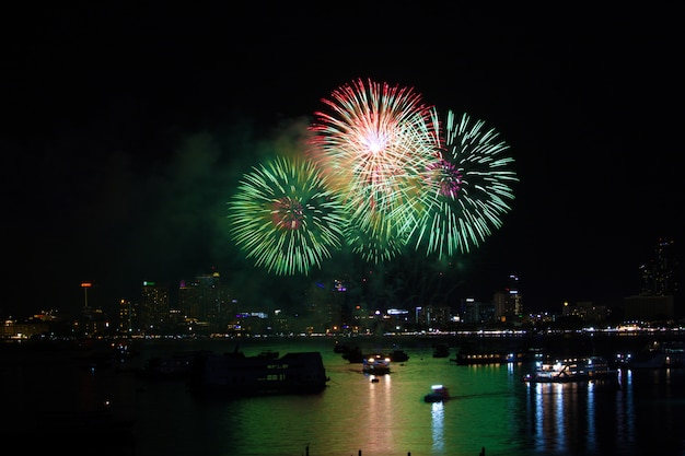 ビーチにマゼンタの緑の花火と水面に反射色 Premium写真