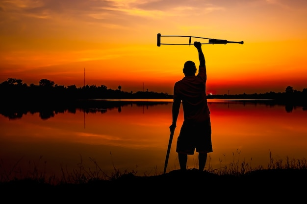 日の出の背景に松葉杖を持つ障害のある男。 Premium写真