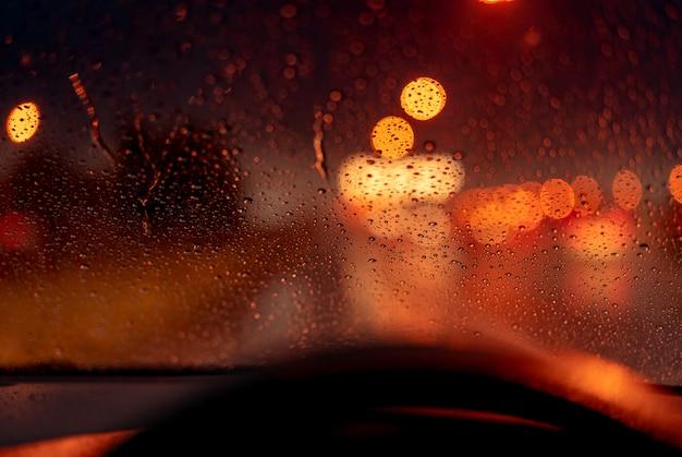 交通渋滞の日に街路灯からオレンジ色の夜の光ボケ。雨の日。雨滴の透明なガラス窓。ロマンチックな天気。都市生活。 Premium写真