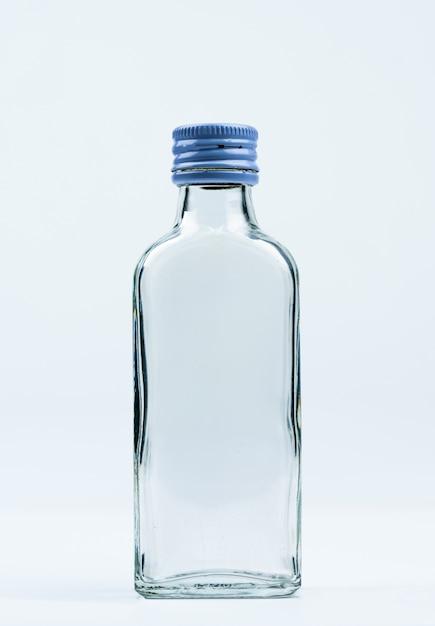 Пустая прозрачная стеклянная бутылка с закрытой алюминиевой крышкой с пустой этикеткой и копией пространства Premium Фотографии