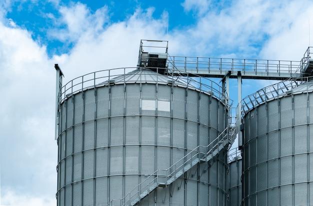 飼料工場の農業用サイロ。飼料製造における貯蔵穀物用の大きなタンク Premium写真