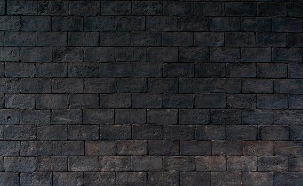 Предпосылка текстуры черной и коричневой кирпичной стены грубая. темная кирпичная стена для скорби эмоциональной. внешняя архитектура. Premium Фотографии