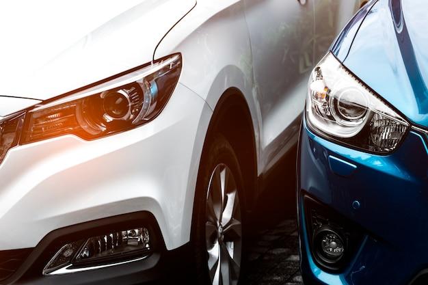 Крупным планом фары свет синий и белый внедорожник, припаркованный на конкретной стоянке отеля или торгового центра. концепция автомобильной промышленности. технология электрических или гибридных автомобилей. концепция проката автомобилей. Premium Фотографии