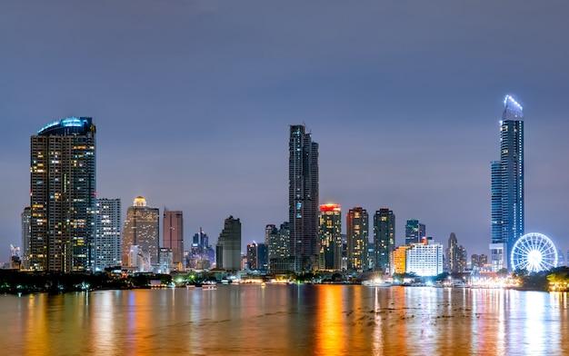 Городской пейзаж современного здания возле реки в ночное время. современная архитектура офисного здания. небоскреб с вечерним небом. черно-белые тона изображения. ночная съемка здания набережной. Premium Фотографии