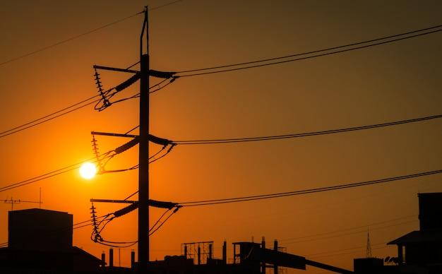市内の高圧電柱と送電線。日没時の電気の鉄塔。パワーとエネルギー。エネルギー資源の保護。配電所でのワイヤーケーブル付きの高電圧タワー。 Premium写真