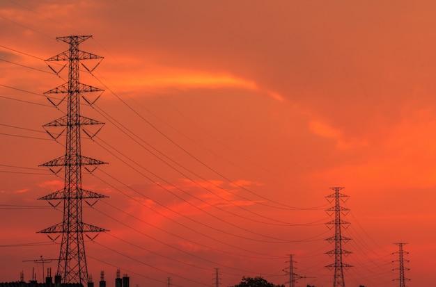 夕方には高圧電柱と送電線。日没時の電気の鉄塔。パワーとエネルギー。エネルギー資源の保護。配電所でのワイヤケーブルを備えた高電圧グリッドタワー。 Premium写真