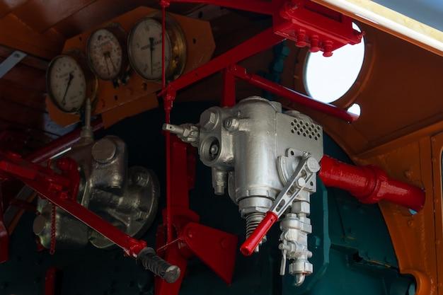 蒸気機関車のクローズアップ制御バルブ。方向性バルブにより、蒸気機関車のエンジン駆動システムに蒸気を流すことができます。鉄道輸送産業。列車は炉油で作動しました。 Premium写真