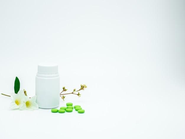Зеленые таблетки с витаминами и добавками для таблеток с цветами и ветками и пустые этикетки на белом фоне с копией пространства, просто добавьте свой собственный текст Premium Фотографии