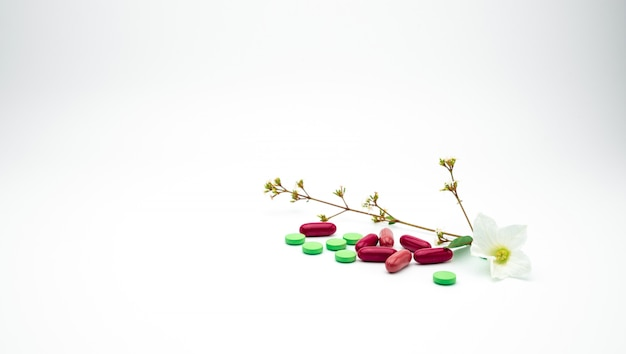 Красные, зеленые таблетки витамина и дополнения и пилюльки капсулы с цветком и ветвь на белой предпосылке с космосом экземпляра. Premium Фотографии