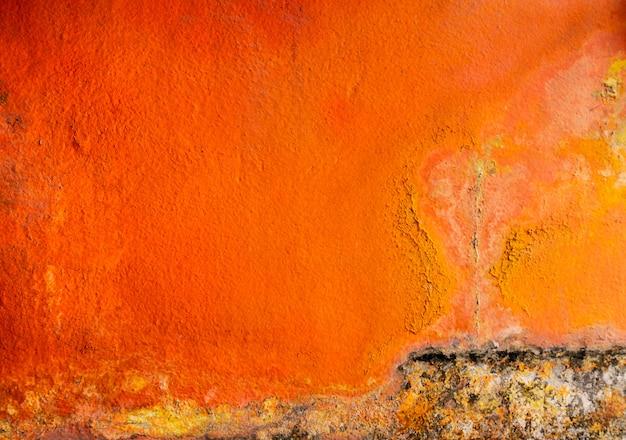 Старый и пакостный оранжевый цвет покрашенный на предпосылке текстуры бетонной стены с космосом. Premium Фотографии