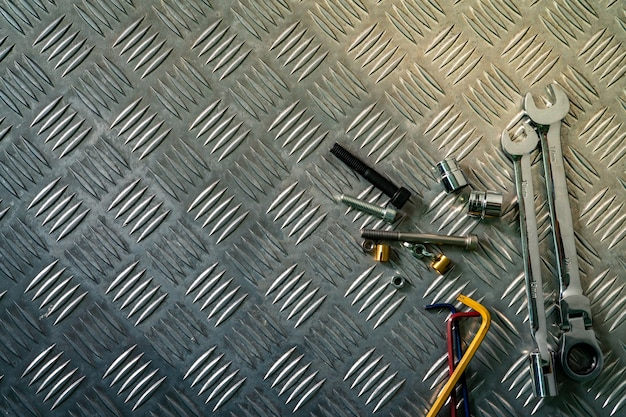 Взгляд сверху инструментов на промышленной плите контролера металла. металлическая шахматная доска для противоскольжения. гайка, болты и шестигранный ключ на металлическом листовом полу. серебряная шишка Premium Фотографии