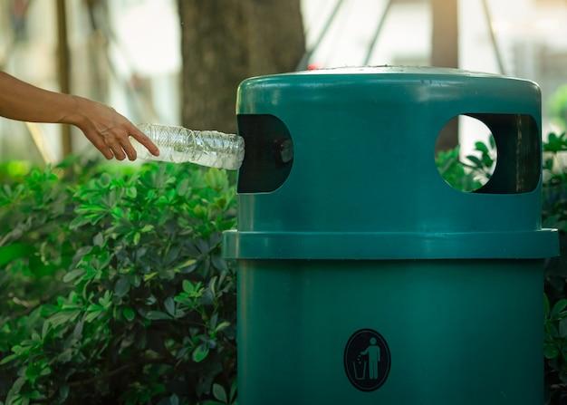 Люди вручают бросать пустую бутылку с водой в мусорную корзину на парк. зеленая пластиковая корзина. человек выбросить бутылку в мусорное ведро Premium Фотографии