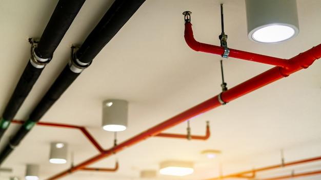 自動火災スプリンクラー安全システムと黒水冷却供給パイプ。消火。防火および探知器。赤いパイプを備えた火災スプリンクラーシステム。 Premium写真
