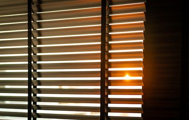 Открытые венецианские пластиковые жалюзи с солнечным светом по утрам. белое пластиковое окно с жалюзи. дизайн интерьера гостиной с оконными горизонтальными жалюзи. Premium Фотографии