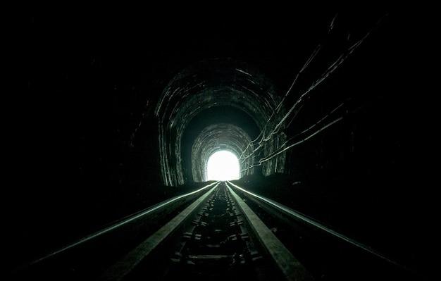 鉄道トンネル。洞窟の古い鉄道。道の終わりに人生の希望。 Premium写真