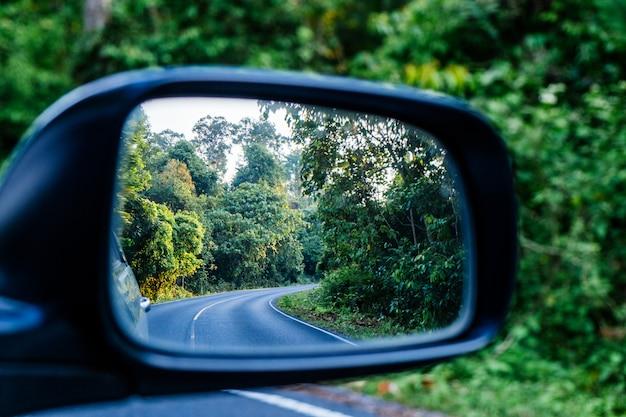 森の中のカーブ道路のサイドミラー反射。 Premium写真