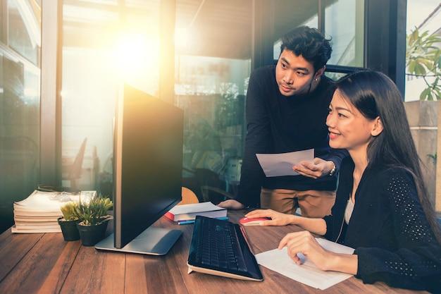 Азиатские молодые внештатные мужчина и женщина, работающая на компьютере в домашнем офисе Premium Фотографии