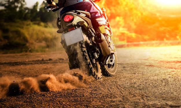人間の乗馬スポーツオートバイの汚れフィールドでツーリング Premium写真