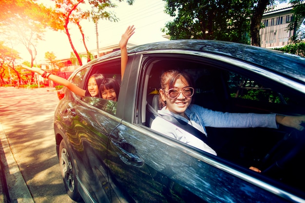 アジアの女性が助手席で幸福ティーンエイジャーで車を運転 Premium写真