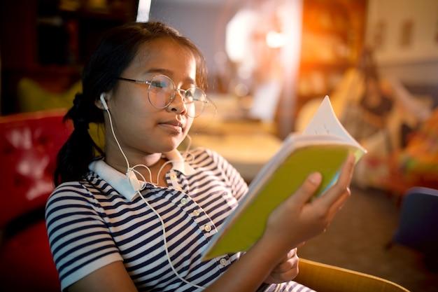 Азиатская девушка читает учебник в домашней комнате Premium Фотографии