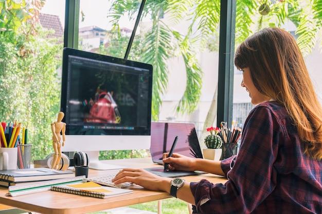 グラフィックデザイナーは、コンピュータとマウスのペンデザイン製品とウェブサイトで作業する Premium写真