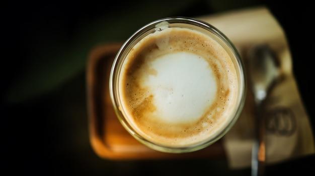 テーブルの上のカップでホットコーヒーカフェラテのクローズアップ。上面図。カフェやレストランのシーン Premium写真