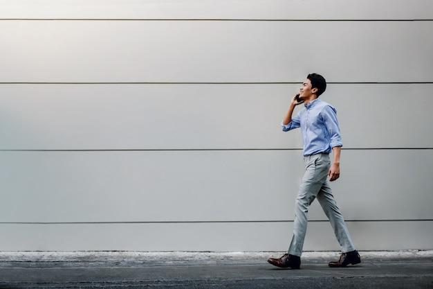 Счастливый молодой бизнесмен в повседневной одежде с помощью мобильного телефона во время прогулки по городской стене здания. образ жизни современных людей. Premium Фотографии